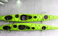 Green kayaks hanging on wall.