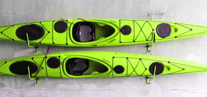 Green kayaks hanging on wall.